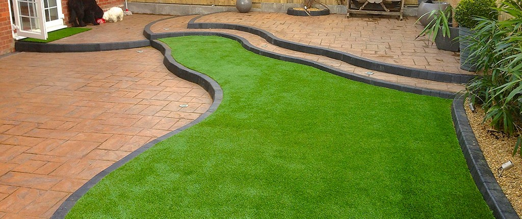 tiered garden featured with artificial grass and stone paving in South Wales
